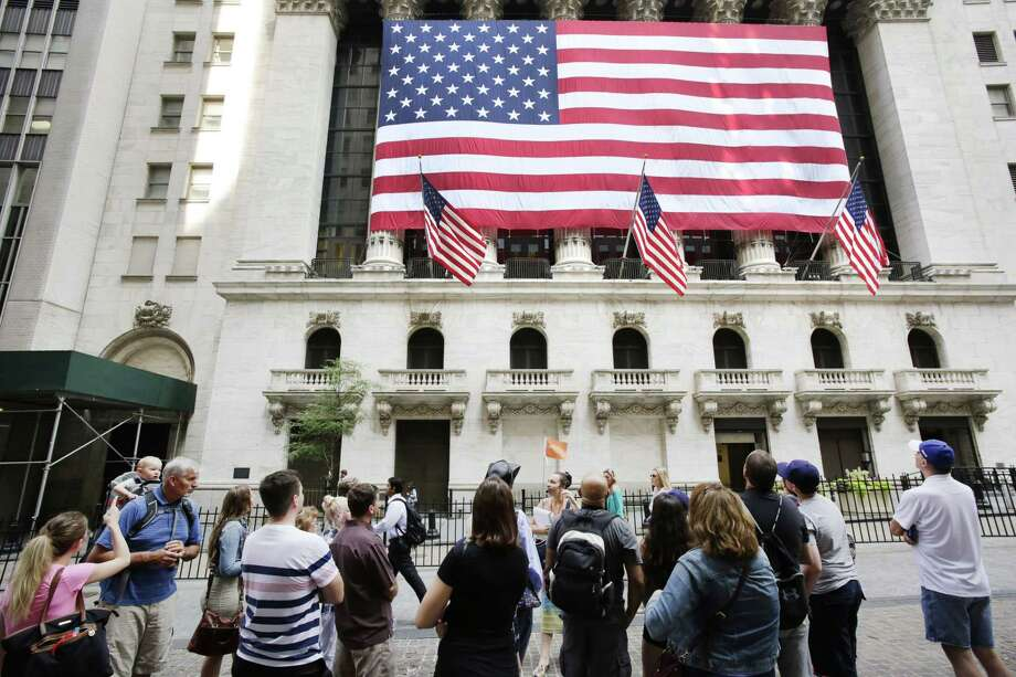 In this July 6, 2015 photo, tourists gather in front of the New York Stock Exchange. Shares sank Wednesday, Aug. 12, 2015 as China let its currency fall for a second day following a surprise devaluation that rattled global financial markets. Photo: AP Photo/Mark Lennihan, File   / AP
