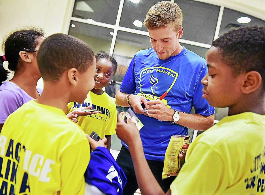 New Haven native Cas Loxsom, 24, a professional middle distance runner signs autographs for Alana Taylor, 9, Anna Pham, 9, Angel Perez, 10 and Matthew Walker, 12, members of the New Haven Age Group Track Club at Wilbur Cross High School, Wednesday, September 9, 2015, in the school auditorium. (Catherine Avalone/New Haven Register) Photo: Journal Register Co. / Catherine Avalone/New Haven Register