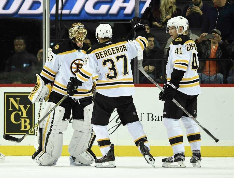 Bruins goalie Tuukka Rask (40), center Patrice Bergeron (37) and left wing Joonas Kemppainen (41) celebrate their 2-1 win over the Islanders on Sunday in New York. Photo: Kathy Kmonicek — The Associated Press    / FR170189 AP