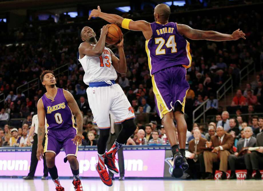 Lakers forward Nick Young (0) watches as Lakers forward Kobe Bryant (24) defends Knicks guard Jerian Grant in the second half Sunday. Photo: Kathy Willens — The Associated Press   / AP