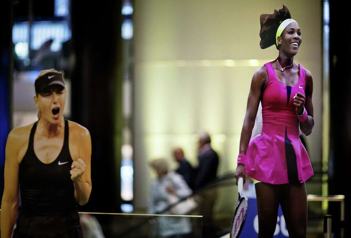 Cutouts of Serena Williams, right, and Maria Sharapova, left, stand in a hotel lobby Thursday in New York. Williams will have to wait before continuing her bid for a calendar-year Grand Slam. Both semifinals scheduled for Thursday were postponed because of rain.