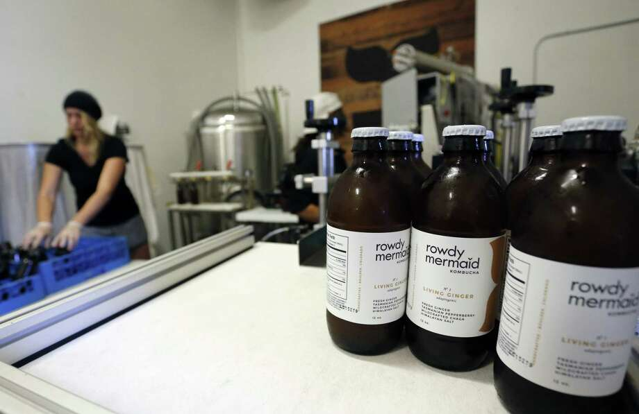 Employee Hannah Melby works Oct. 6 on a bottling run of Living Ginger, one of several kombucha varieties produced at Rowdy Mermaid, a kombucha manufacturer in Boulder, Colo. The tangy, probiotic fermented tea called kombucha has moved from America's natural foods aisle to the mainstream. Photo: Associated Press   / AP