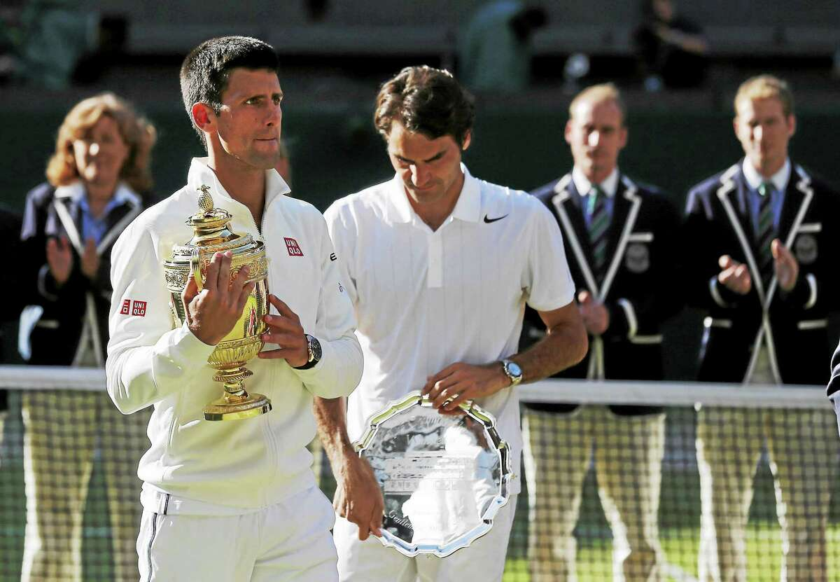 Novak Djokovic, left, holds the trophy after defeating Roger Federer in the men's singles final at the All England Lawn Tennis Championships in Wimbledon, London, on July 6, 2014.