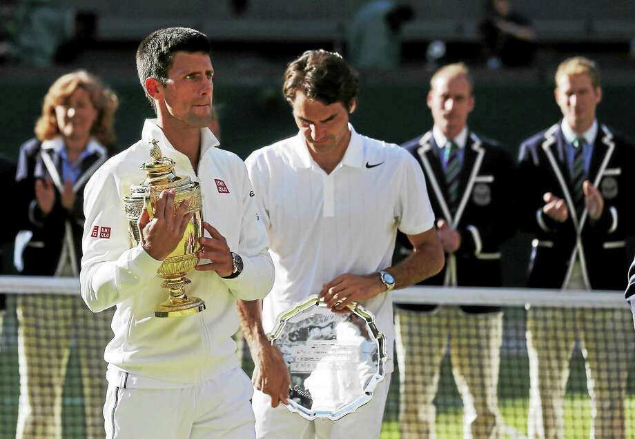 Novak Djokovic, left, holds the trophy after defeating Roger Federer in the men's singles final at the All England Lawn Tennis Championships in Wimbledon, London, on July 6, 2014. Photo: Ben Curtis — The Associated Press File Photo   / AP