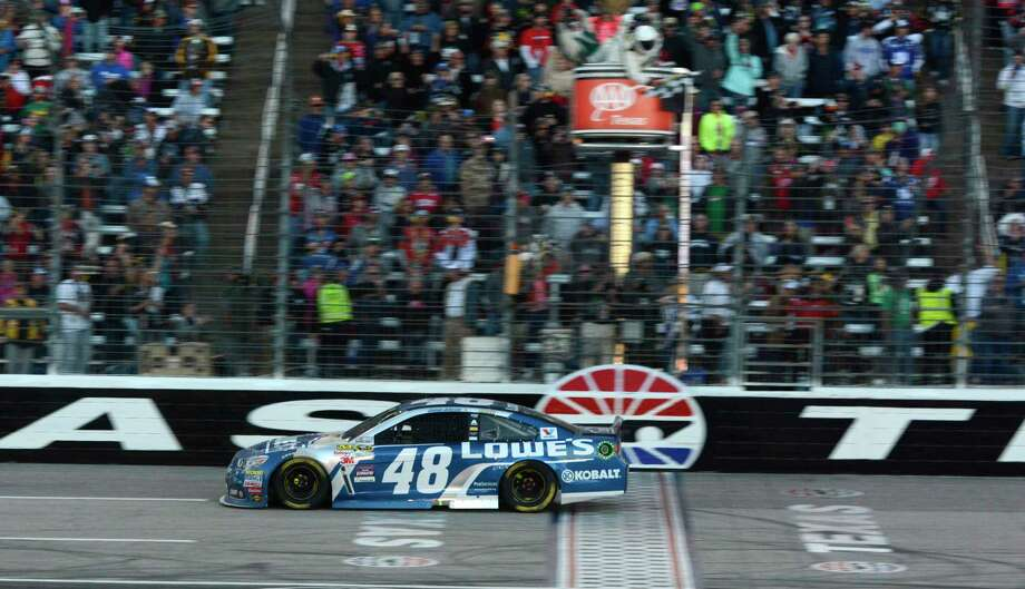 Jimmie Johnson (48) takes the checked flag while winning at Texas Motor Speedway on Sunday. Photo: Larry Papke — The Associated Press   / FR58581 AP