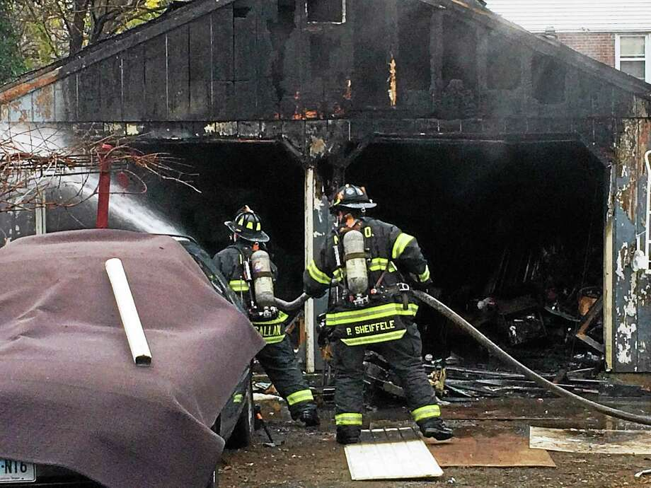 A fire severely damaged a detached garage at 260 Edgewood Ave. in New Haven early Wednesday afternoon. Firefighters were able to bring it under control quickly and a rabbit and chicken behind the garage were unharmed. Photo: (Wes Duplantier -- New Haven Register)
