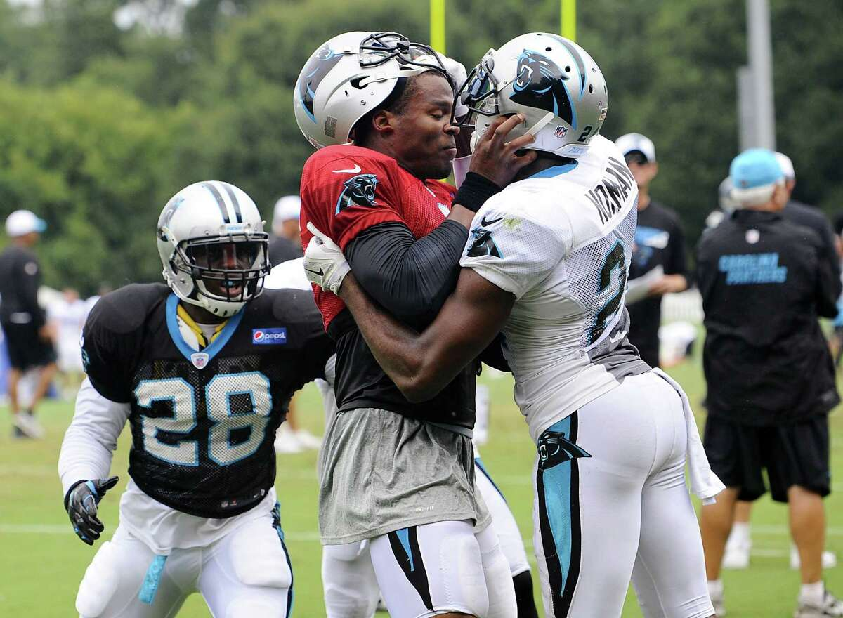 Carolina Panthers quarterback Cam Newton (1) and cornerback Josh Norman (24) scuffle Monday at training camp at Wofford College in Spartanburg, S.C.