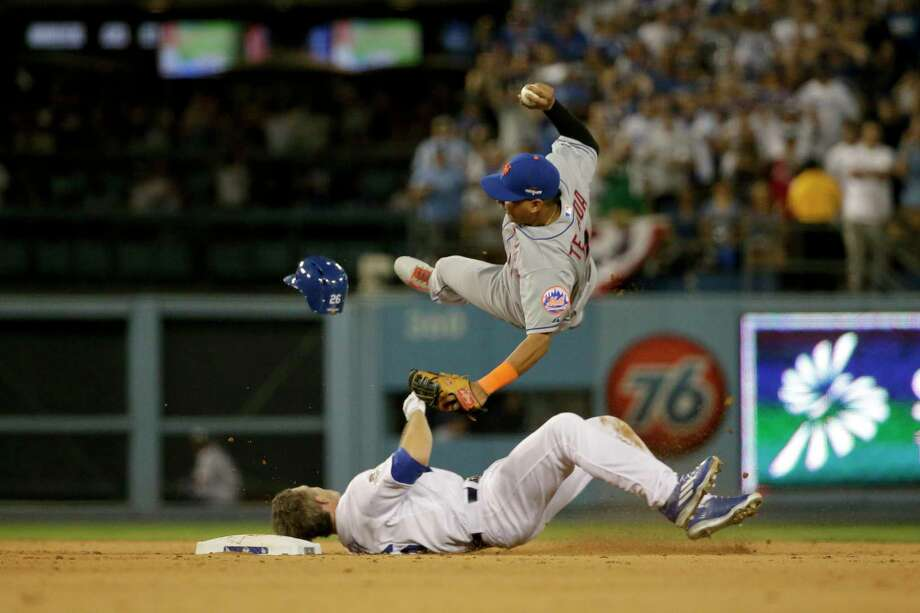 Mets shortstop Ruben Tejada goes over the top of the Dodgers' Chase Utley in the seventh inning Saturday night. Photo: Gregory Bull — The Associated Press   / AP