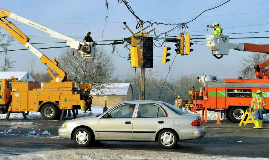 In this Oct. 31, 2011 photo, a vehicle passes under a traffic light damaged by a storm as department of transportation and power workers repair downed lines on Route 5 in South Windsor, Conn. The state's largest electrical utility collaborated with the University of Connecticut to open the Eversource Energy Center at UConn in October 2015, devoted to studying ways to better predict and prepare the state's power infrastructure for natural disasters. Photo: AP Photo/Jessica Hill, File   / FR125654 AP