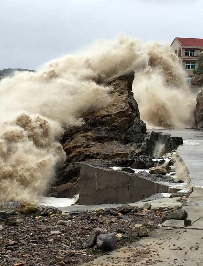 A strong wave breaks on shore ahead of the landfall of Typhoon Chan-Hom in Wenling in eastern China's Zhejiang province on Friday, July 10, 2015. Chinese authorities have evacuated tens of thousands of people and canceled scores of trains as a super-typhoon with wind gusts up to 200 kilometers per hour (125 mph) heads toward the southeastern coast. (Chinatopix Via AP) CHINA OUT Photo: AP / CHINATOPIX
