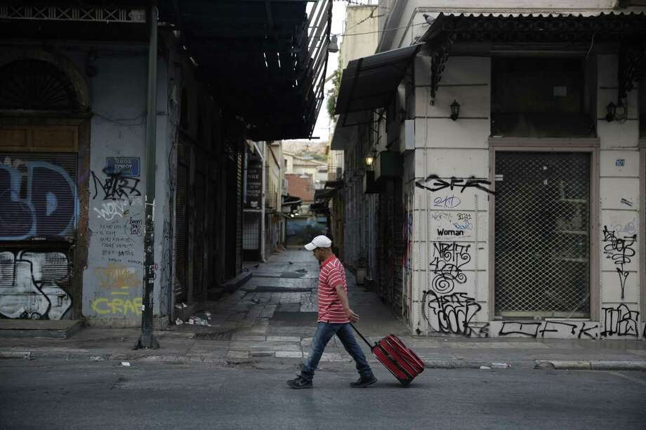 A man carries a luggage in central Athens, Saturday, July 11, 2015. Greece's negotiators head to Brussels on Saturday armed with their reform proposals and parliamentary backing to seek a third bailout, but with the shadow of severe dissent from governing lawmakers hanging over them. (AP Photo/Petros Giannakouris) Photo: AP / AP