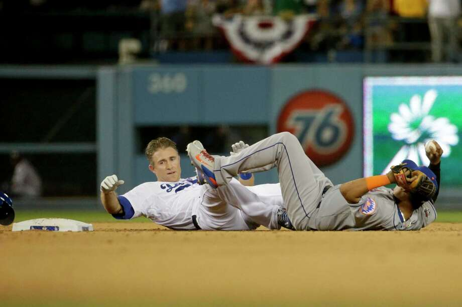 Mets shortstop Ruben Tejada, right, lands next to the Dodgers' Chase Utley during the seventh inning in Game 2 of the NLDS on Saturday. Photo: The Associated Press   / AP