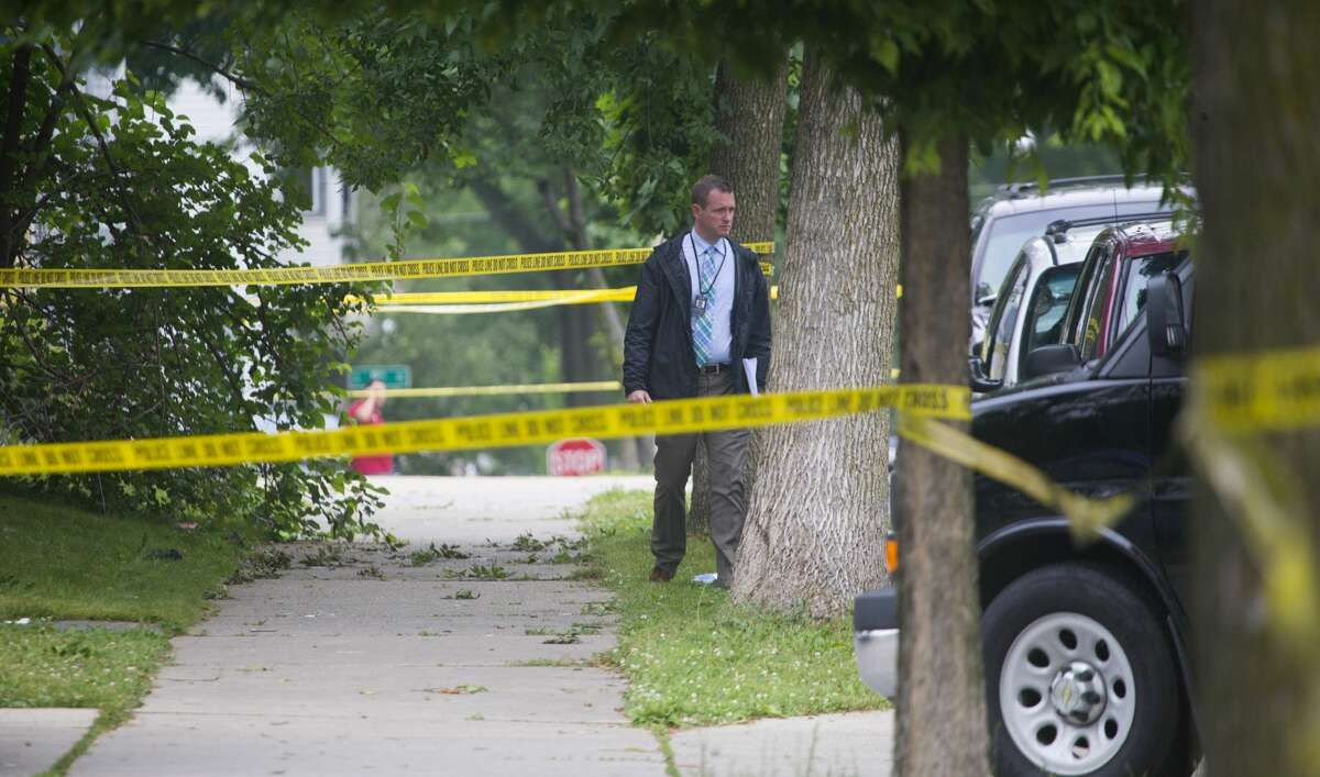 In this July 7, 2015 photo, authorities work the scene of a double homicide in Milwaukee. Police departments across the country that in recent years have been boasting about plummeting crime numbers now find themselves scrambling to deal with something they haven't seen in years: More bloodshed. (Mark Hoffman/Milwaukee Journal Sentinel via AP)