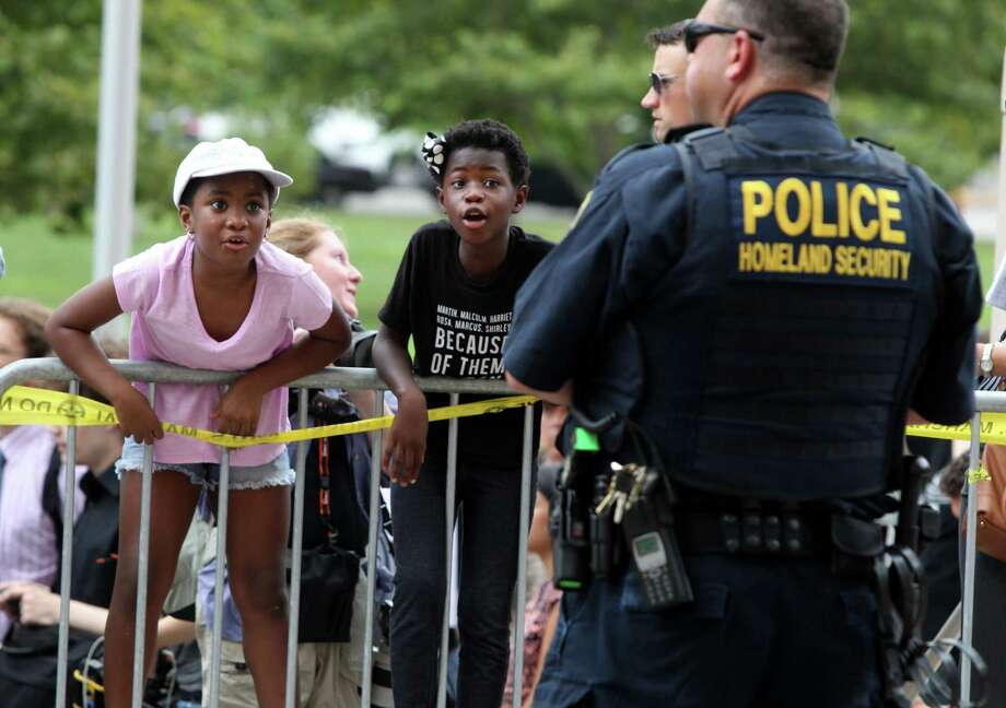 McKenzie Davis, left, and Alice Dowd, chant at an officer as a crowd of protesters gathers as officers stand watch Monday, Aug. 10, 2015, in St. Louis. Protesters have been arrested after blocking the entrance to the St. Louis federal courthouse while calling for more aggressive U.S. government response to what they call racist law enforcement practices. Photo: Christian Gooden/St. Louis Post-Dispatch Via AP / St. Louis Post-Dispatch