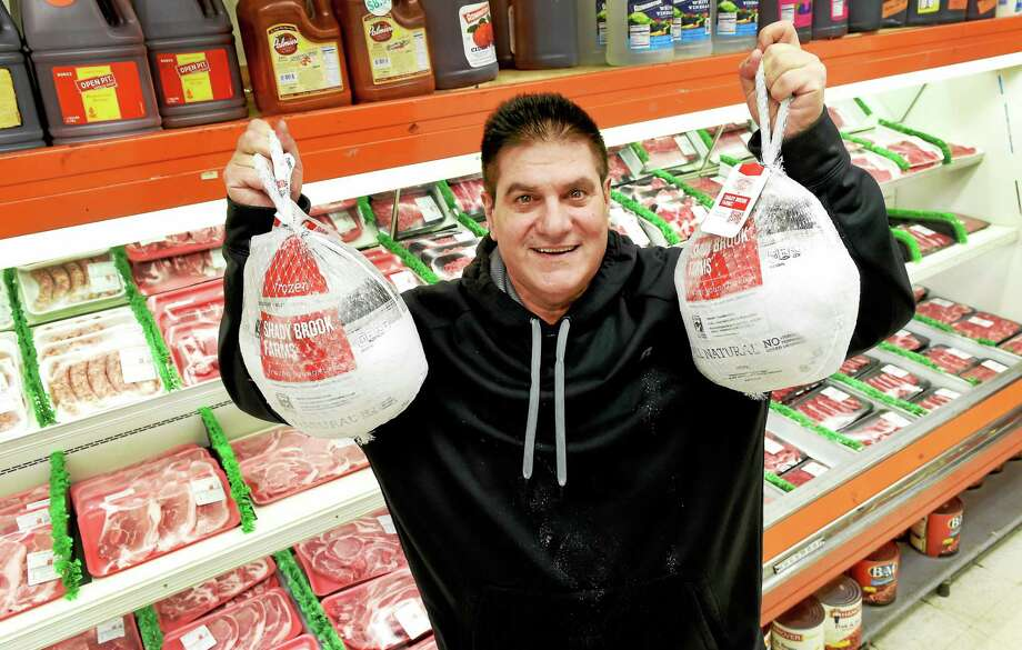 (Peter Hvizdak - New Haven Register)Frank Minore of Minore's Meats on Whalley Ave. in New Haven holds 12-pound turkeys in his market Friday November 7, 2015. Turkey prices are excepted to be high this Thanksgiving season. Photo: ©2015 Peter Hvizdak / ©2015 Peter Hvizdak