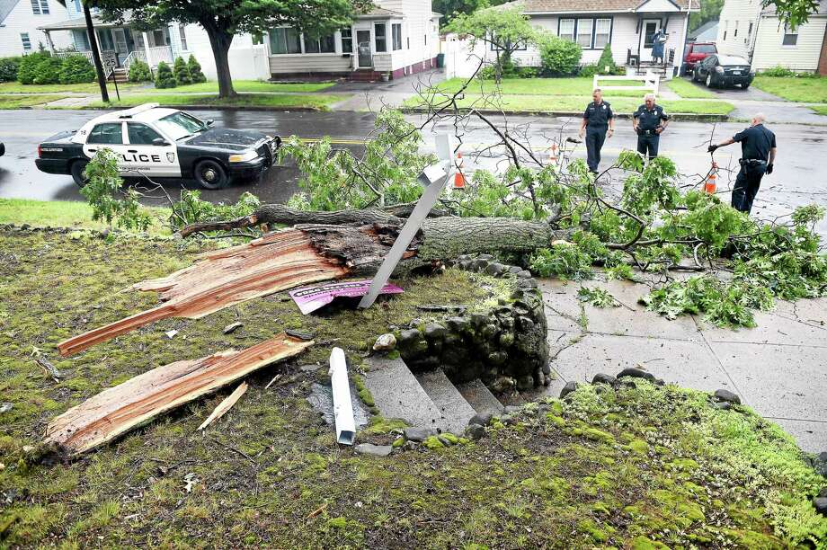 West Haven Police place cones around a downed tree at the corner of Kelsey Avenue and Church Street Tuesday. Photo: Arnold Gold — New Haven Register