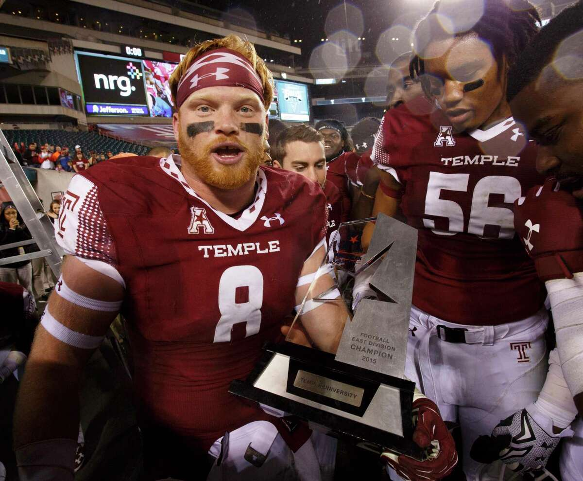 Temple linebacker Tyler Matakevich holds the AAC East Division trophy following a 27-3 win over UConn on Nov. 28 in Philadelphia.