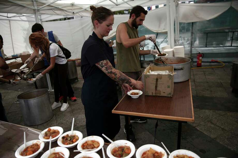 Volunteers serve meals made with 'wasted' produce deemed unsuitable by food stores because of their appearance, during an event against food waste, in Athens, Greece on Oct. 11, 2015. The event was part of the 'Feeding5000' campaign which aims to highlight the waste of foodstuff in advanced societies. Photo: AP Photo/Yorgos Karahalis   / AP
