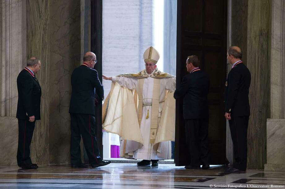 Pope Francis pushes open the Holy Door of St. Peter's Basilica, formally launching the Holy Year of Mercy, at the Vatican, Tuesday, Dec. 8, 2015. Francis stood in prayer on the threshold of the basilica's Holy Door then walked through it, the first of an estimated 10 million faithful who will pass through over the course of the next year in a rite of pilgrimage dating back centuries. Photo: L'Osservatore Romano/Pool Photo Via AP    / L'Osservatore Romano