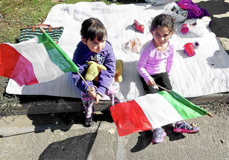 (Arnold Gold-New Haven Register)  Gianna Cicarella (left), 5, and Delaney Shepard, 5, of East Haven watch the Greater New Haven Columbus Day Parade as it passes on Hemingway Avenue in East Haven Sunday. Photo: Journal Register Co.