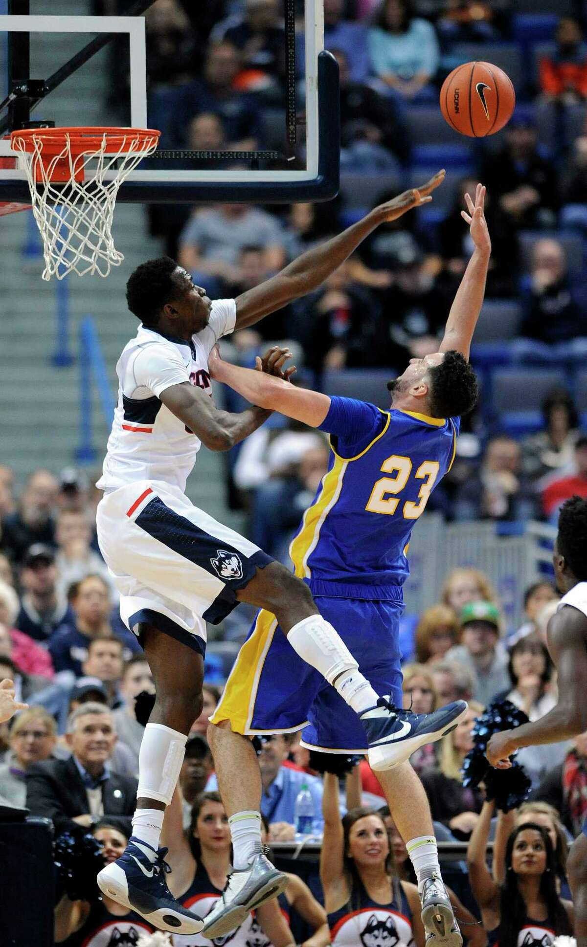 Connecticut's Amida Brimah (35) blocks the shot of New Haven's Joshua Guddemi (23) during the first half of an NCAA college basketball exhibition game in Hartford, Conn., on Saturday, Nov. 7, 2015. (AP Photo/Fred Beckham)