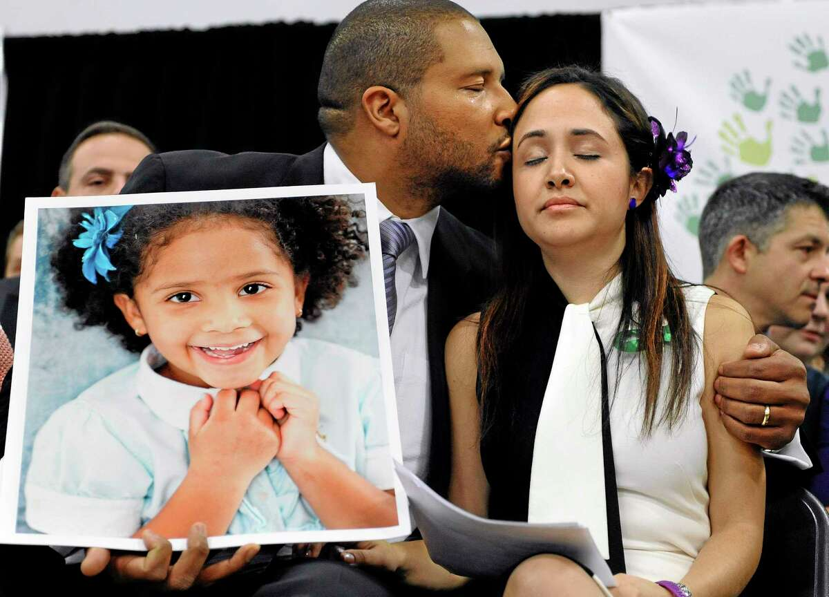 Jimmy Greene, left, kisses his wife Nelba Marquez-Greene as he holds a portrait of their daughter, Sandy Hook School shooting victim Ana Marquez-Greene at a news conference at Edmond Town Hall in Newtown, Conn. on Jan. 14, 2013. One month after the mass school shooting at Sandy Hook Elementary School, the parents joined a grassroots initiative called Sandy Hook Promise to support solutions for a safer community.