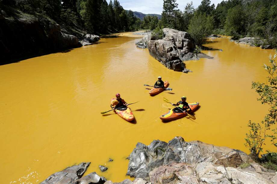 FILE - In this Thursday, Aug. 6, 2015 file photo, people kayak in the Animas River near Durango, Colo., in water colored yellow from a mine waste spill. A crew supervised by the U.S. Environmental Protection Agency has been blamed for causing the spill while attempting to clean up the area near the abandoned Gold King Mine. Tribal officials with the Navajo Nation declared an emergency on Monday, Aug. 10, as the massive plume of contaminated wastewater flowed down the San Juan River toward Lake Powell in Utah, which supplies much of the water to the Southwest. Photo: (Jerry McBride/The Durango Herald Via AP, FILE) / The Durango Herald