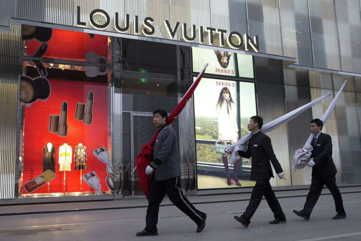 In this photo taken Monday, March 16, 2015, Chinese staff from a shopping mall walk past a flagship store of french luxury brand Louis Vuitton in Beijing. Counterfeiting is a big business, by one estimate, the global market for fakes will hit $1.7 trillion this year.