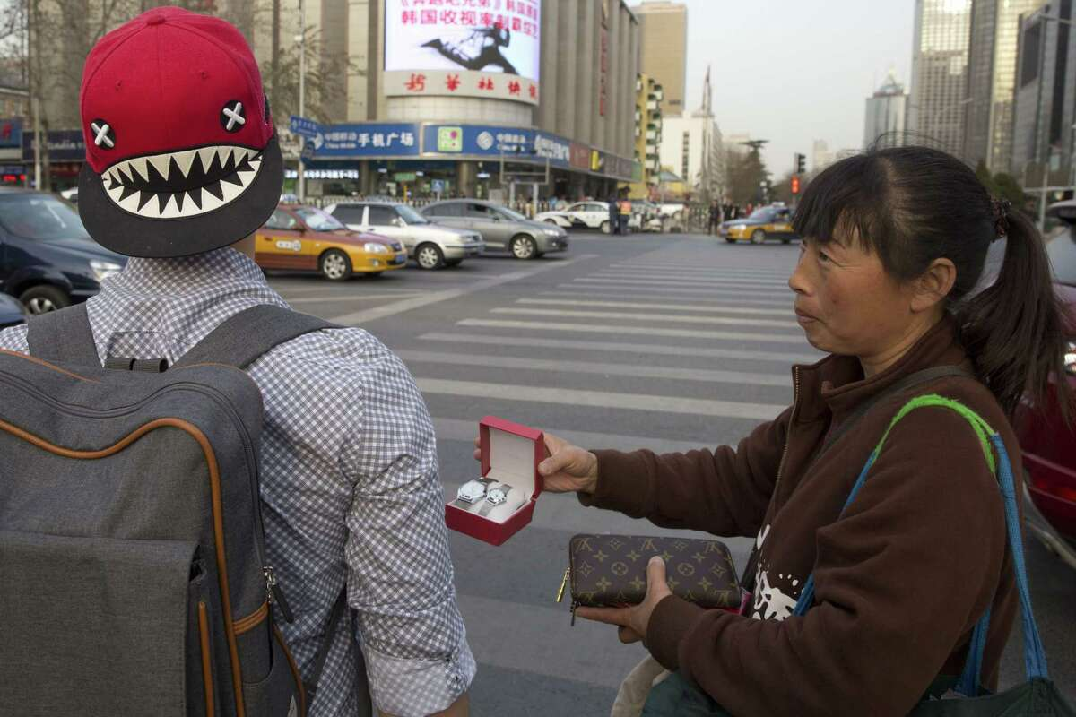 In this photo taken Friday, March 20, 2015, a street vendor hawks counterfeit branded items to tourists on the streets of Beijing. Counterfeiting is a big business, by one estimate, the global market for fakes will hit $1.7 trillion this year.