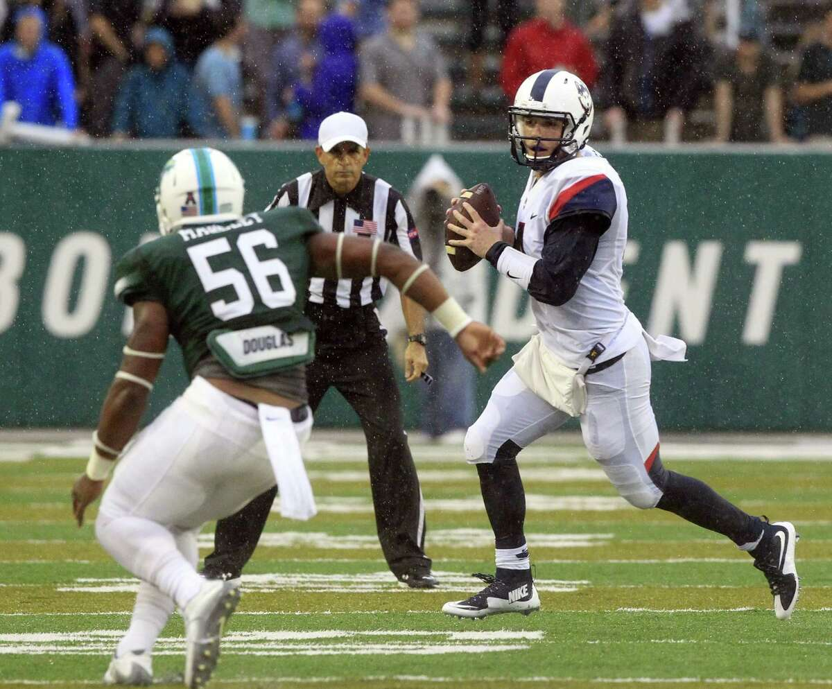 UConn quarterback Bryant Shirreffs (4) scrambles out of the pocket as Tulane linebacker Rae Juan Marbley (56) closes in during Saturday's game.