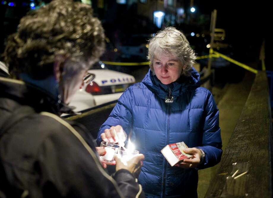 """In this photo taken Monday night, Nov. 30, 2015, DJ Thomson, right, and Joyce Levine light candles on Kennedy Street after hearing about the death of Mayor Stephen """"Greg"""" Fisk in Juneau, Alaska. Fisk, the newly elected mayor of Alaska's capital city, was found dead in his home Monday. Circumstances surrounding the death were not immediately known. Photo: Michael Penn/The Juneau Empire Via AP    / The Juneau Empire"""