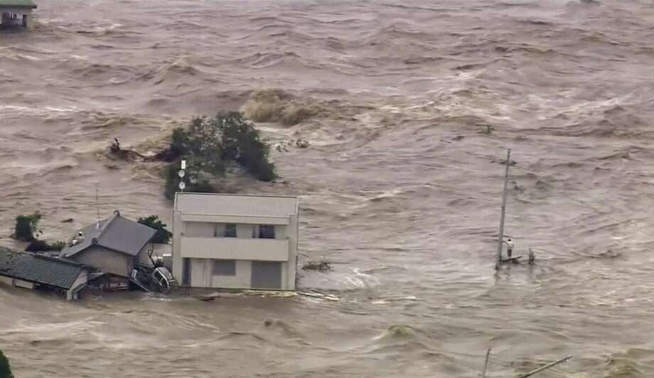 TBS TV via AP   In this photo taken from video provided by Japan's Tokyo Broadcasting System (TBS) television network, a man, right, stands stranded in the middle of raging floodwaters before being rescued by a military helicopter in Joso, Ibaraki prefecture, Thursday, Sept. 10, 2015. Raging floodwaters broke through a berm Thursday and swamped the city near Tokyo, washing away houses, forcing dozens of people to rooftops to await helicopter rescues and leaving one man clinging for his life to a utility pole. Photo: AP / TBS TV via AP