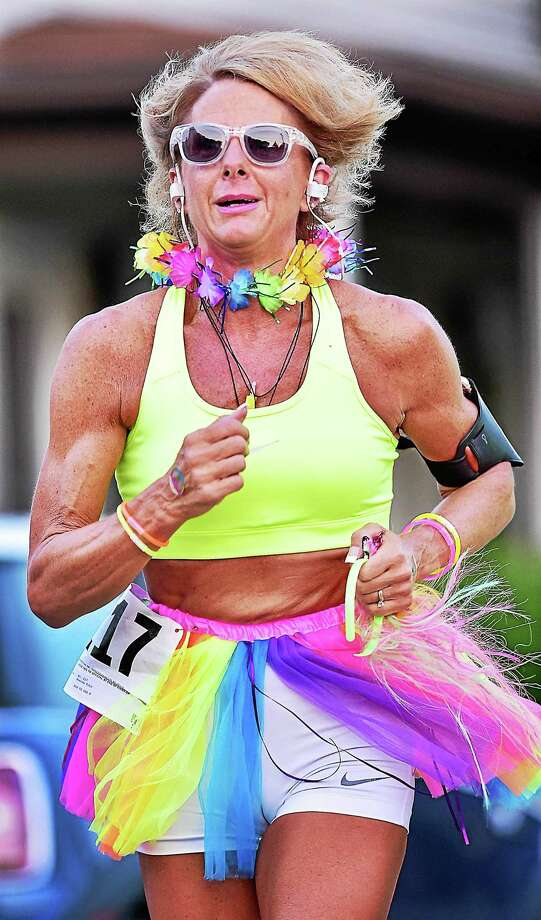 Milford resident Brenda Toto runs up Lafayette Street in the Literacy Center of Milford's annual 5k Neon Night Run, Saturday, July 11, 2015. Photo: (Catherine Avalone/New Haven Register) / Catherine Avalone/New Haven Register