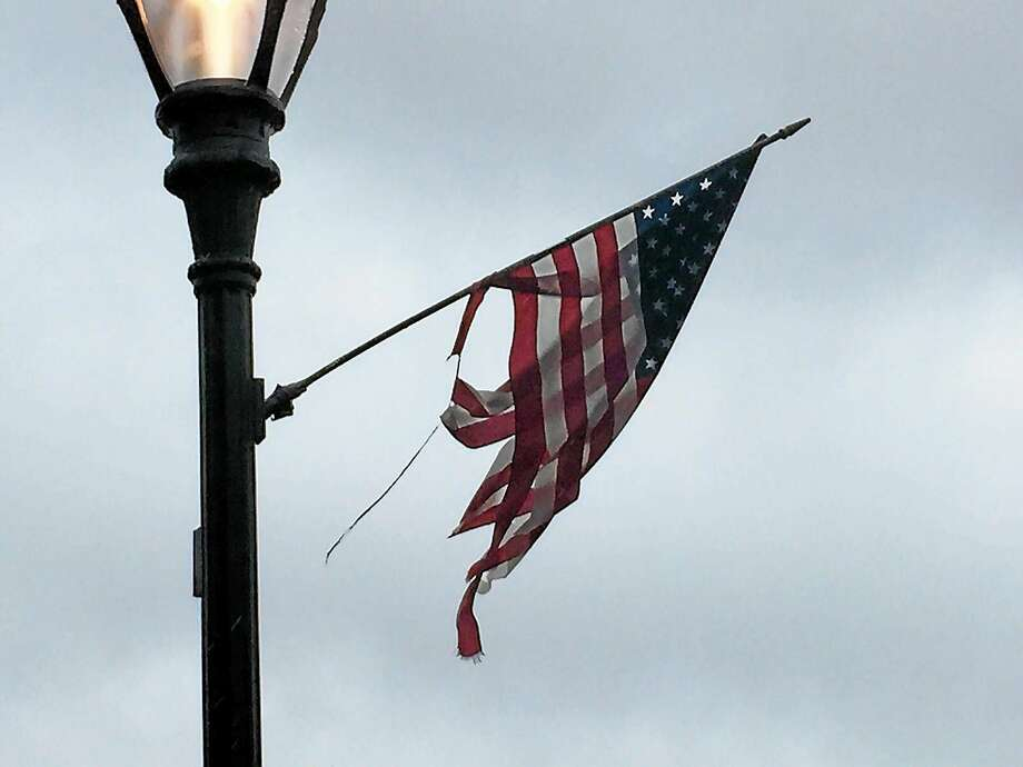 Most of the two dozen flags hanging from the black light posts that line Main Street are either tattered and torn, have broken sticks that have been pieced together with duct tape or are laying on the ground. Photo: Contributed Photo