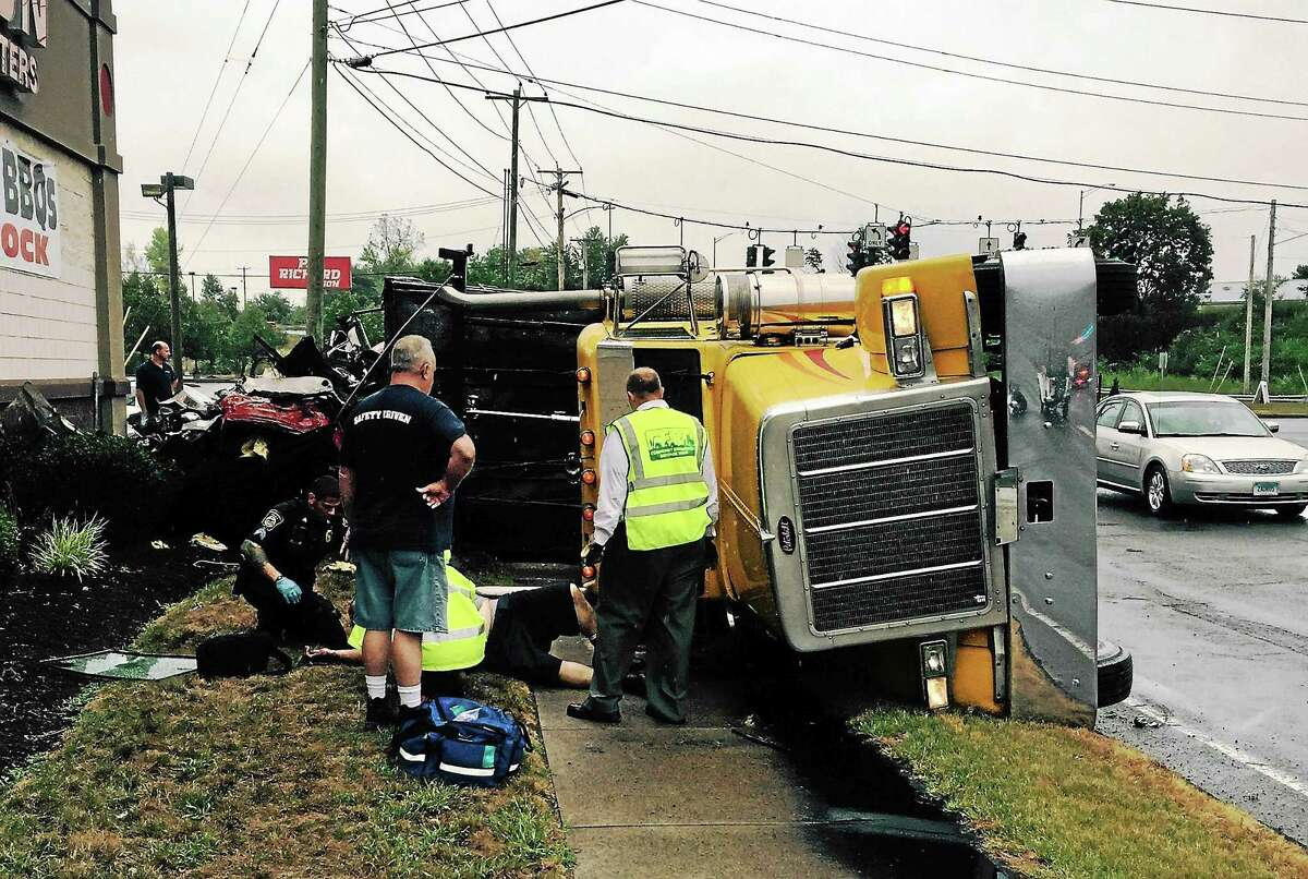 Emergency crews work to help two men after a truck rolled on its side Thursday afternoon on Universal Drive in North Haven.