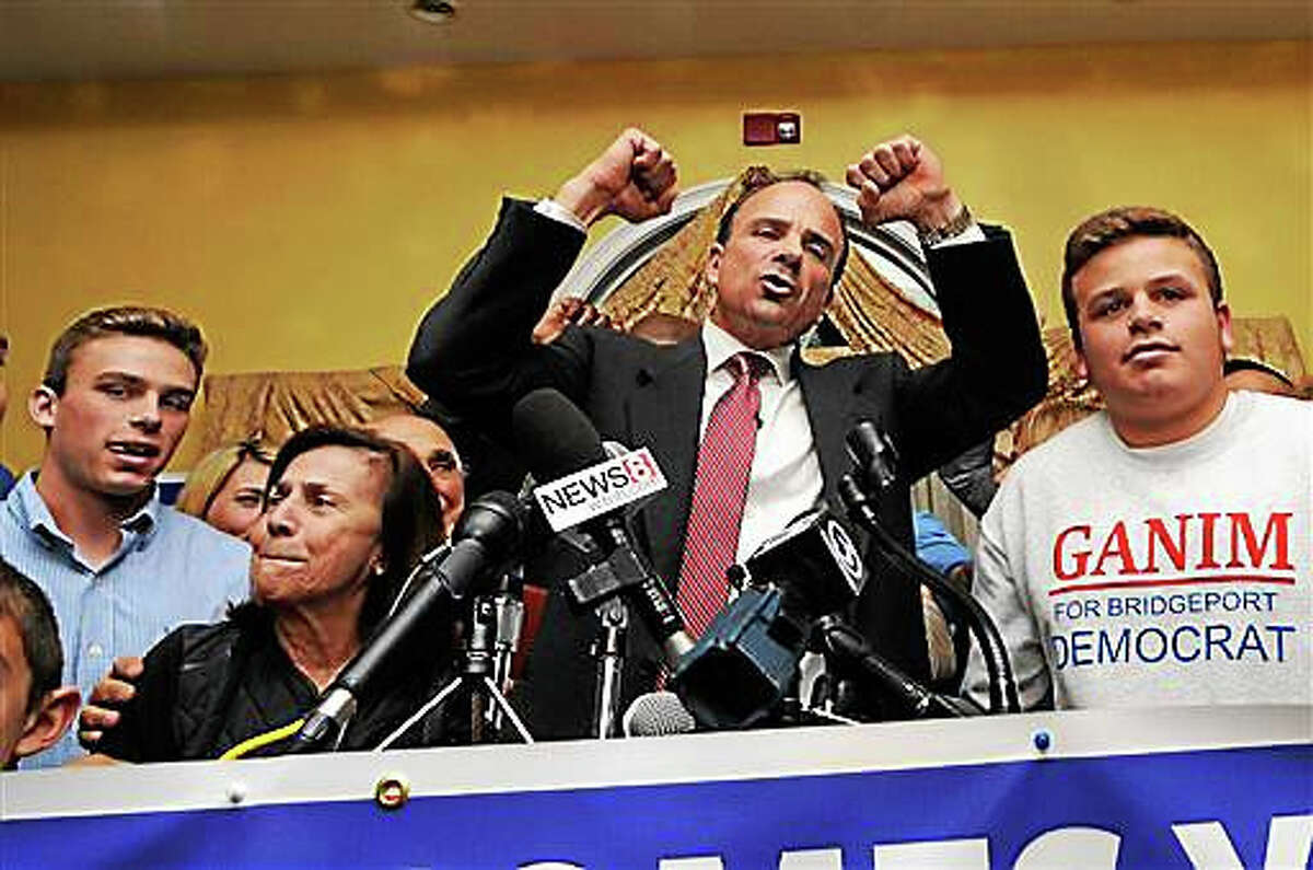 Democrat Joe Ganim celebrates with his son Rob and other supporters after winning the election as Bridgeport's new mayor at Testo's Restaurant in Bridgeport, Conn., Tuesday, Nov. 3, 2015. Ganim, an ex-convict who spent seven years in federal prison for corruption, reclaimed the Bridgeport mayor's office Tuesday, completing a stunning comeback bid that tapped nostalgia for brighter days in Connecticut's largest city.