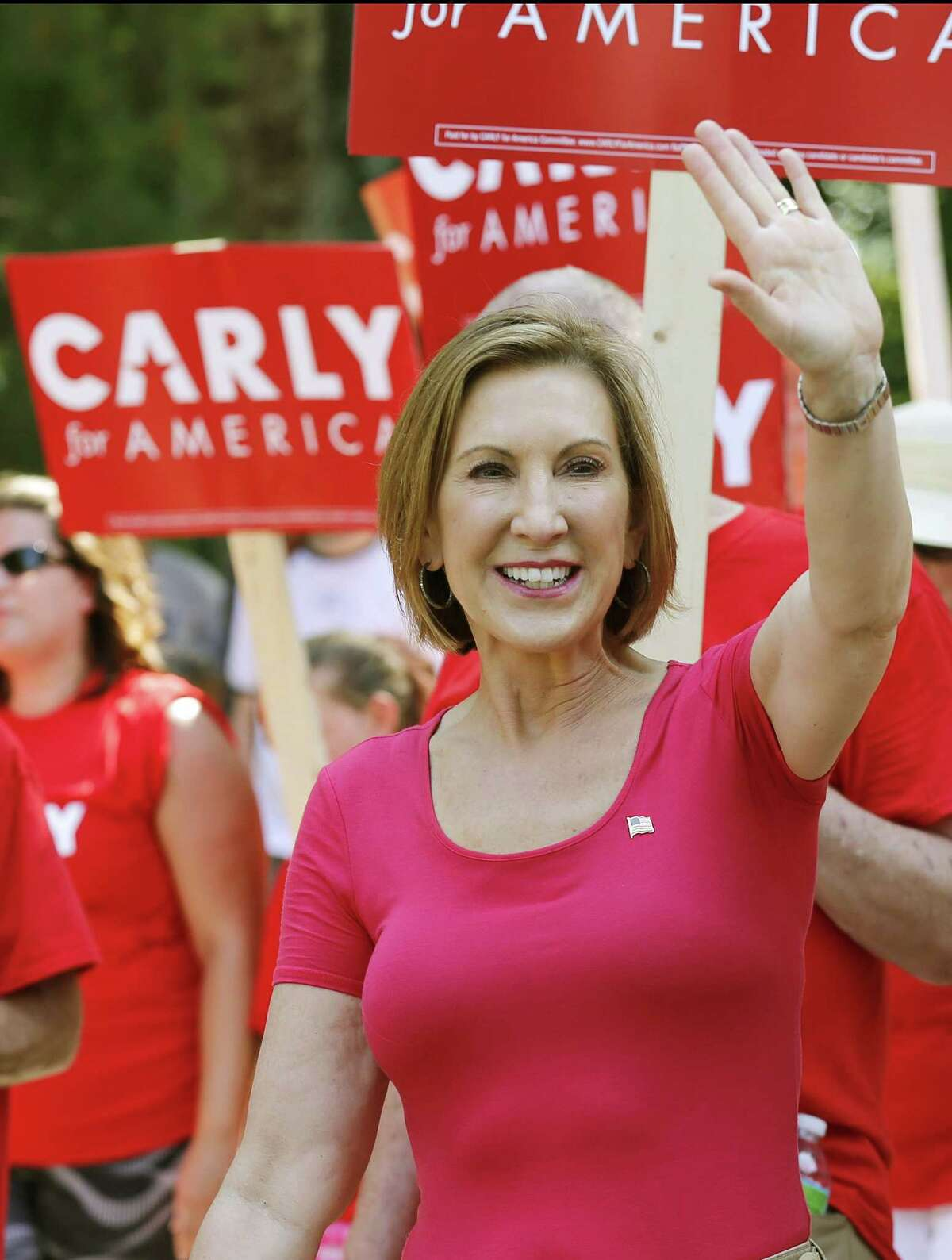 Republican presidential candidate Carly Fiorina, the former Hewlett-Packard chief executive waves as she and supporters march in the Labor Day parade Monday, Sept. 7, 2015, in Milford, N.H.