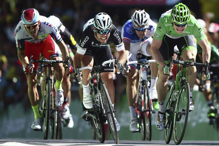 Mark Cavendish celebrates as he crosses the finish line ahead of Andre Greipel, wearing the best sprinter's green jersey, and Alexander Kristoff, left, to win the seventh stage of the Tour de France on Friday. Photo: Peter Dejong — The Associated Press   / AP