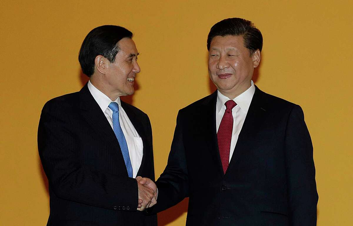 Chinese President Xi Jinping, right, and Taiwanese President Ma Ying-jeou, left, shake hands at the Shangri-la Hotel on Saturday, Nov. 7, 2015, in Singapore. The two leaders shook hands at the start of a historic meeting, marking the first top level contact between the formerly bitter Cold War foes since they split amid civil war 66 years ago.