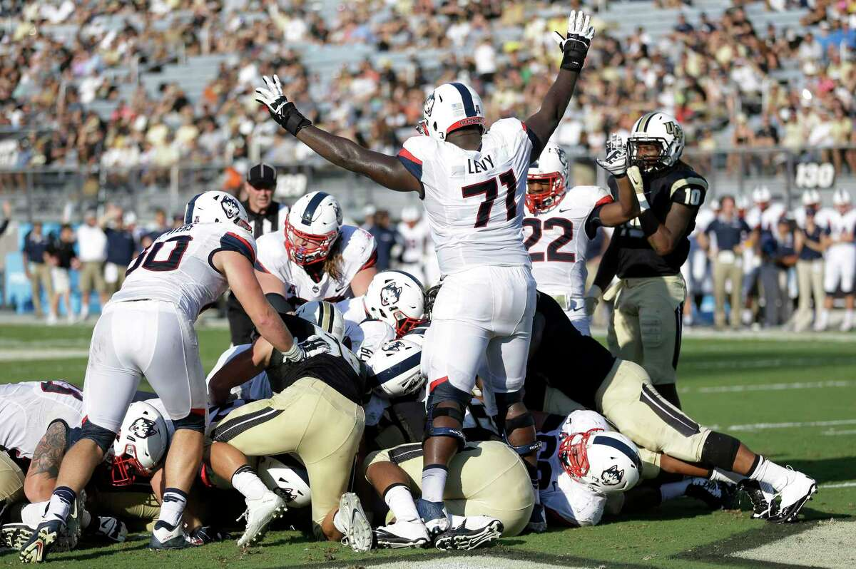 UConn offensive lineman Richard Levy (71) signals a touchdown as quarterback Bryant Shirreffs dives in the pile on a quarterback sneak for a score on Saturday.