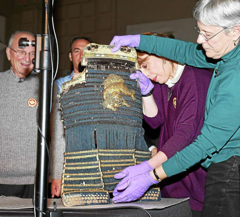 """Adrienne Saint-Pierre, right, curator of the Barnum Museum, and conservator Catherine Sease, far right, of the Yale Peabody Museum of Natural History remove a front piece from a Samurai suit of armor during the program, """"Revealed! Secrets of a Samurai Box,"""" at the Yale Peabody Museum of Natural History. Photo: Arnold Gold — New Haven Register"""