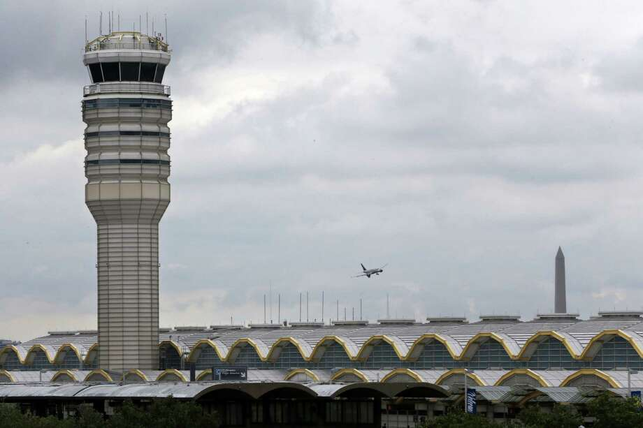An airplane flies between the air traffic control tower and the Washington Monument at Washington's Ronald Reagan National Airport, Aug. 10, 2015. For more than three years, the government has kept secret a study it requested that found air traffic controllers' work schedules often lead to chronic fatigue, making them less alert and endangering the safety of the national air traffic system, according to report on the study obtained by The Associated Press. Photo: AP Photo/Jacquelyn Martin / AP