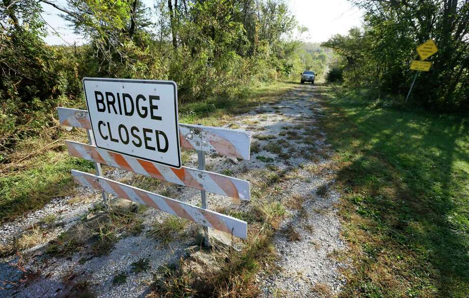Duane Ohnemus drives his truck down a dirt road around a bridge closed sigh near his farm in Milo, Iowa. The bridge closure has caused problems for Ohnemus and his wife, Mary Jo, who raise cattle, corn and soybeans on 1,500 acres their family has owned for more than a century. Photo: Charlie Neibergall — The Associated Press   / AP