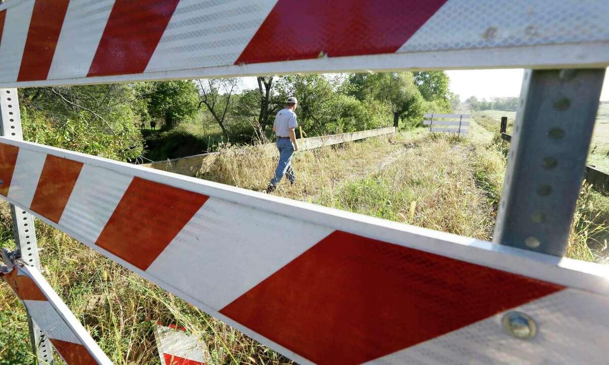 Duane Ohnemus walks on a closed bridge on a dirt road near his farm in Milo, Iowa.