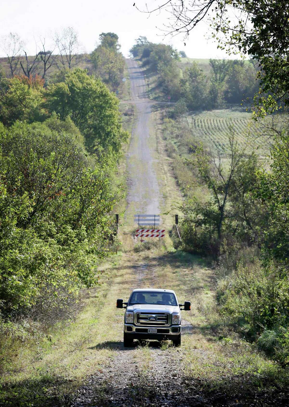 Duane Ohnemus drives his truck away from a closed bridge on a dirt road near his farm in Milo, Iowa.
