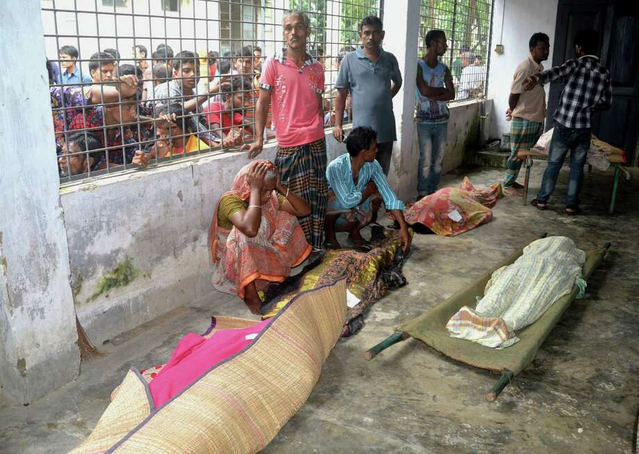 An elderly woman grieves next dead bodies at Mymensingh Medical College Hospital in the town of Mymensingh, 115 kilometers (70 miles) north of Dhaka, Bangladesh, Friday, July 10, 2015.  The victims died on a stampede when hundreds of people stormed the home of a businessman for a charity handout during the holy Muslim month of Ramadan, police said. (AP Photo/Jahangir Kabir Jewel) Photo: AP / AP