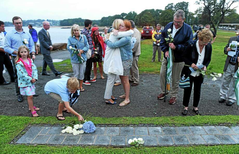 Debra Woodward, center, of Fairfield and her niece, Emma Hunt, 15, embrace in front of the plaque for Emma's father, Will Hunt, during the state's 9/11 Memorial Ceremony at Sherwood Island State Park in Westport Thursday. Photo: Arnold Gold — New Haven Register