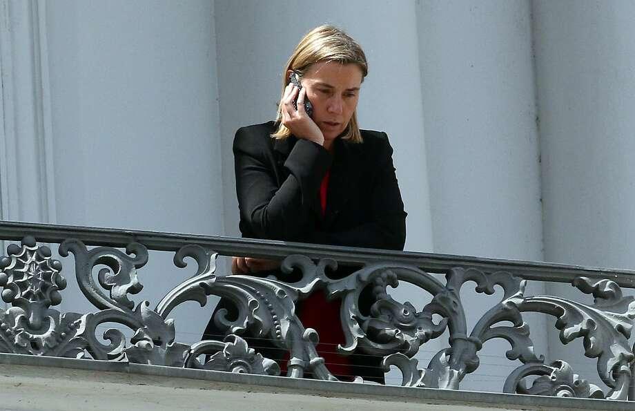 European Union High Representative Federica Mogherini make a phone call on a balcony of the Palais Coburg where closed-door nuclear talks with Iran take place in Vienna, Austria, Friday, July 10, 2015. (AP Photo/Ronald Zak) Photo: AP / AP