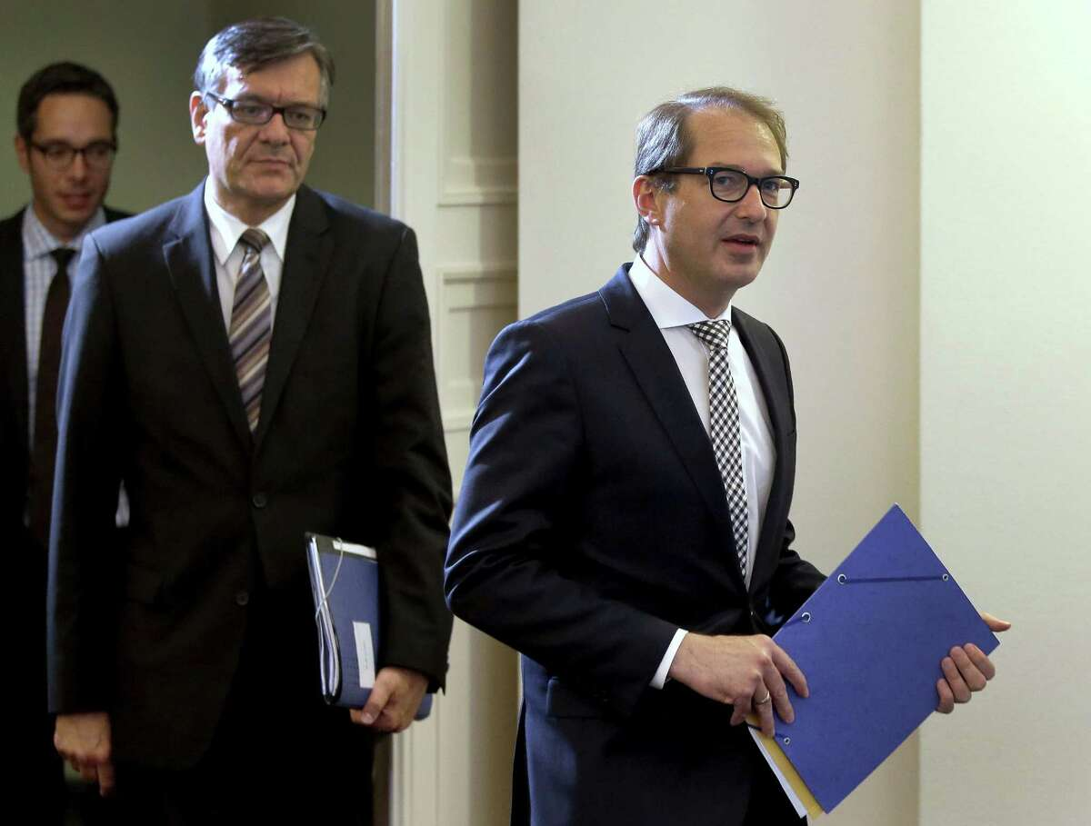 German Transportation and Digital Infrastructure Minister Alexander Dobrindt, left, and Matthias von Randow, Executive Director of the German Aviation Association, right, hold files as they arrive for a joint press conference where they presented an interim report of a task force group on the Germanwings crash, in Berlin, Germany, Tuesday, June 30, 2015. Lufthansa offered financial compensation on Tuesday to relatives of people killed in the Germanwings crash three months ago in a proposal that a lawyer representing many German families immediately described as inadequate. (AP Photo/Michael Sohn)