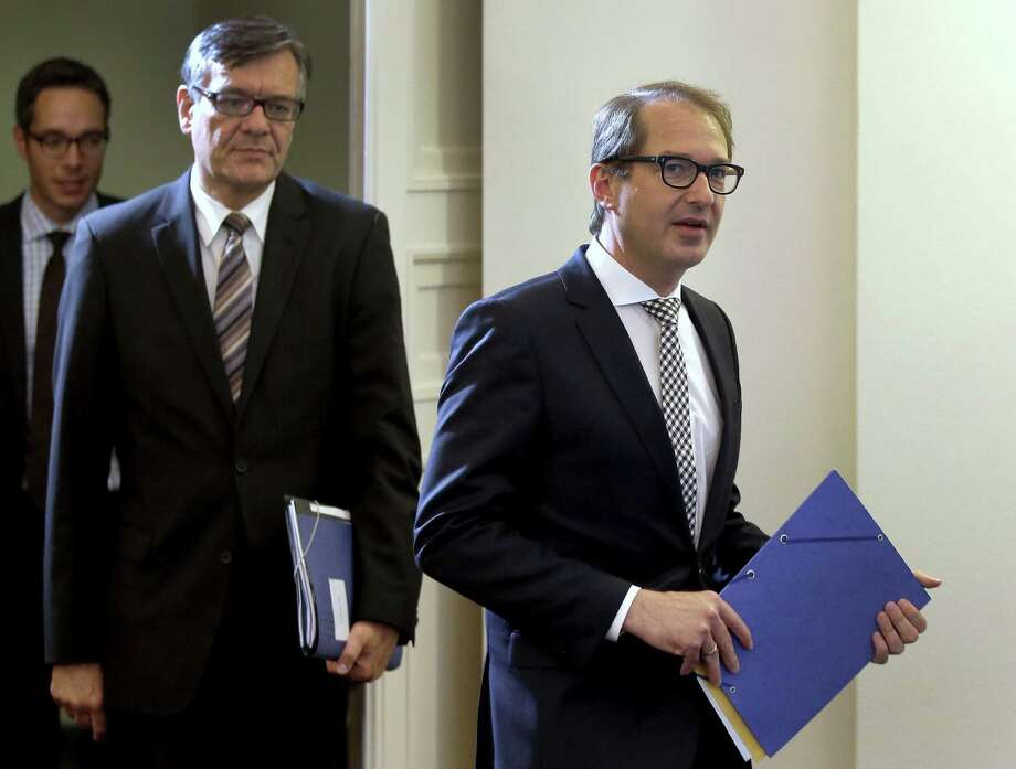 German Transportation and Digital Infrastructure Minister Alexander Dobrindt, left, and Matthias von Randow, Executive Director of the German Aviation Association, right, hold files as they arrive for a joint press conference where they presented an interim report of a task force group on the Germanwings crash, in Berlin, Germany, Tuesday, June 30, 2015. Lufthansa offered financial compensation on Tuesday to relatives of people killed in the Germanwings crash three months ago in a proposal that a lawyer representing many German families immediately described as inadequate. (AP Photo/Michael Sohn) Photo: AP / AP